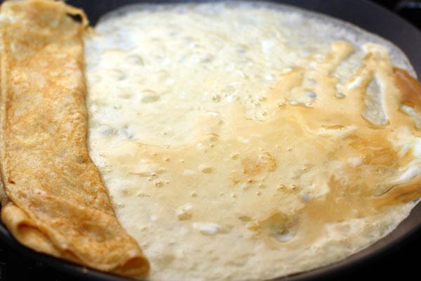 Сдвиньте получившийся сверток к самому краю сковороды, а на свободную часть налейте еще порцию яичной смеси. Новый блинчик должен одним краем приклеиться с первому.