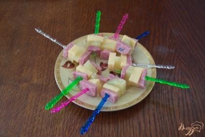 Нанизывайте на каждую шпажку продукты в последовательности: ветчина, сыр, ананас, ветчина. Если шпажка позволяет, можно повторить слои.