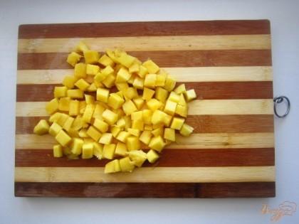 Теперь нужно очистить и нарезать манго. На первый взгляд это легко, но для человека делая это первый раз, дам пару советов. Сначала, манго помойте и очистите от кожицы с помощью овощечистки. У манго очень большая кость, она находится по середине. Поэтому держите фрукт вертикально и срежьте две половины фрукта с обеих сторон, а потом нарежьте кубиком.