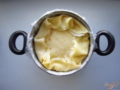 Теперь будем делать дно для нашего торта. Выложите два блина на сметанный слой.Края блинов, что свисали с кастрюли по очереди загибаем, дно торта готово. Что бы торт имел хорошую форму поставьте его в холодильник на 1 час.