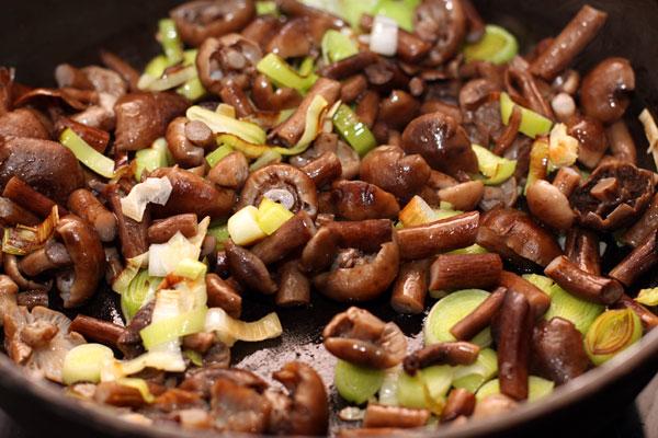 Добавьте к порею вареные опята, порезанные на 2-3 части каждый и продолжайте готовить, помешивая, еще 5 минут.