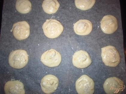 На промасленный пергамент выложите десертной ложкой тесто и посыпьте кокосовой стружкой. Поставьте в нагретую духовку на сначала на 5 минут при 180С, а потом уменьшите до 150 и выпекайте еще минут 7.