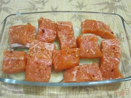 На дно смазанной маслом формы выложить кольца лука, сверху на них - кусочки рыбы.
