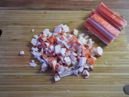 Крабовые палочки мелко порезать и добавить в салатницу
