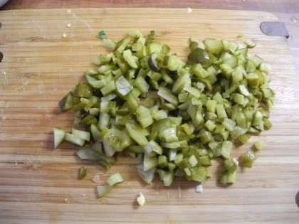 Соленые огурцы мелко порезать и добавить в салатницу