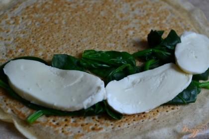 Блин уложить на сковороду с небольшим количеством растительного масла.Только на одну сторону блина положить немного шпината и моцареллу.