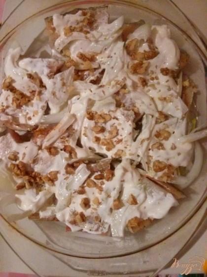 Потом смажьте минтай сметаной. Посыпьте сверху измельченными грецкими орехами.