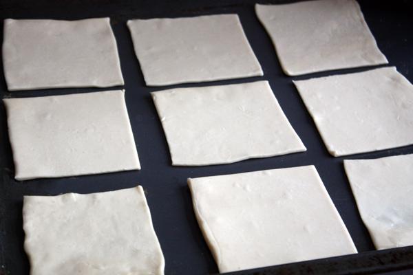 Тесто нужно раскатать толщиной 0,3-0,5 см на слегка посыпанной мукой поверхности и нарезать квадратами примерно 10х10 см.