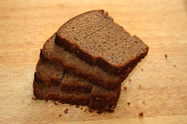 Нарезать хлеб ломтиками толщиной 5 мм, затем его разделить еще на 3 части. Мне нравится делать эти канапешки из бородинского хлеба.