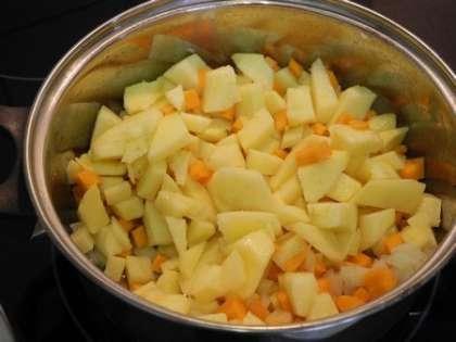В кастрюлю налить масло и сложить овощи