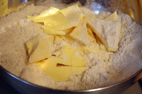 Теперь делаем тесто. Миндаль измельчаем до состояния мелкой крошки, смешиваем с мукой и сахаром. Туда же кладем холодное сливочное масло кусочками.