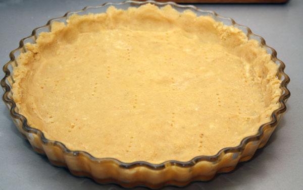 В низкую формую, смазанную маслом, выкладываем тесто и раскатываем его ровным слоем толщиной в 0,5-1 см, с небольшими бортиками.  Делаем несколько проколов вилкой.
