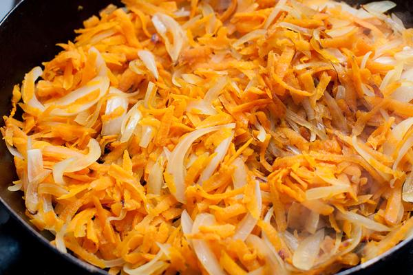 Через 5 минут нам останется только дополнить вкусовую гамму. Для этого в кастрюлю добавляем обжаренные лук и морковь, мелко нарезанный чеснок и соль.