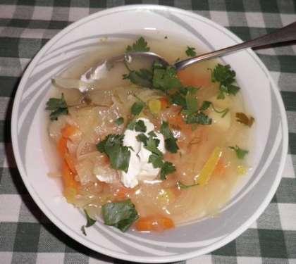 Готовый суп разлить по тарелкам и положить сметану