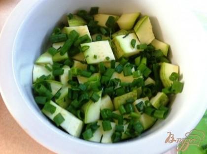 В форму для выпечки выложить часть порезанных кабачков, посыпать зеленым луком