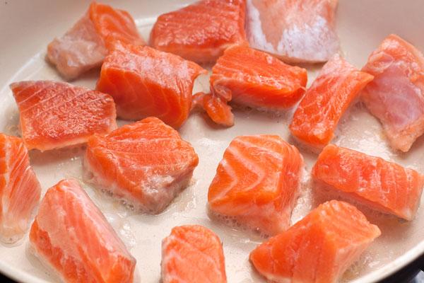 Филе семги нарежьте кубиками и обжарьте со всех сторон до легкой румяности.
