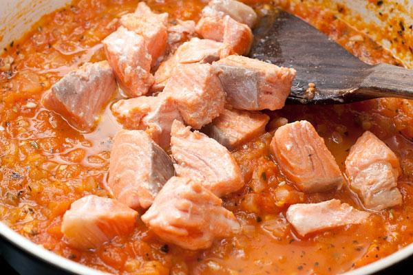 Добавьте рыбу в соус и перемешайте. Посолите, если надо.