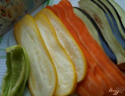 Тонкими пластинами нарезаем овощи: баклажан, кабачок и морковь. Перец разрезаем на 4 части вдоль.