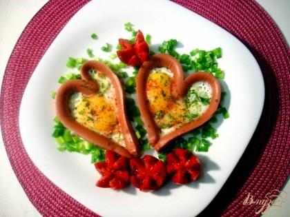 Готово! На тарелочку выкладываем сосиску с яйцом. Вокруг насыпаем зеленый лук. Из помидоров вырезаем цветы.