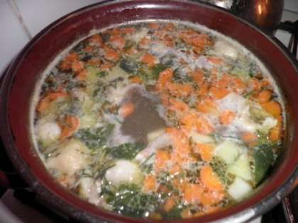 В бульон добавить овощи, бульонные кубики и зелень, добавить фасоль