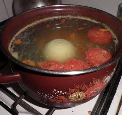 Картофель, морковь и помидор добавить к рыбе, положить бульонный кубик
