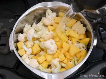 Добавить картофель, цветную капусту, залить кипятком из чайника (так чтобы покрыло овощи).