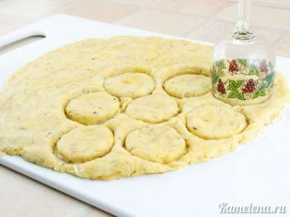 Стол или доску немного посыпать мукой, выложить тесто. Скалку посыпать мукой, раскатать тесто в толстый пласт толщиной примерно 1 см. Вырезать формочкой или бокалом кружки (я использовала бокал диаметром 5 см).