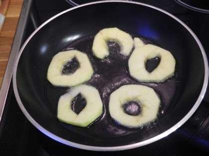 На горячую сковороду налить масло и выложить кружочки из яблок