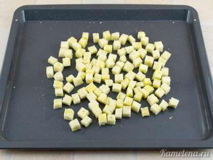 С батона срезать корку, порезать хлеб небольшими кубиками. Разложить на противне, равномерно полить полученным маслом, перемешать.