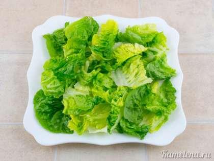 Формируем салат. Салатные листья помыть, обсушить, порвать кусочками и выложить на тарелку.
