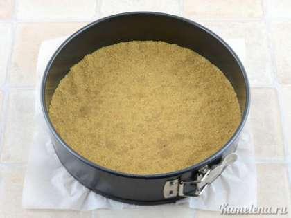 Выложить в форму крошки печенья, плотно утрамбовать руками по дну. Поставить форму в холодильник на время приготовления начинки.