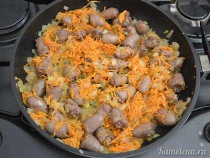 Добавить лук, морковь, перемешать. Жарить 15-20 минут, до мягкости сердечек и овощей.