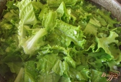 Когда процедите бульон, поставьте его на огонь и вскипятите. Первым положите картофель, следом лук. Жаренный лук тоже можно положить сразу. Когда вода снова закипит выложите листья салата и хорошенько посолите воду.