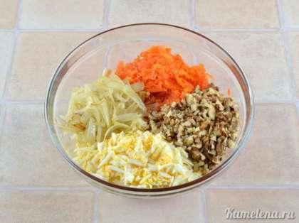 В салатник положить морковь, лук, грецкие орехи, яйца. Посолить, поперчить, полить растительным маслом, хорошо перемешать.