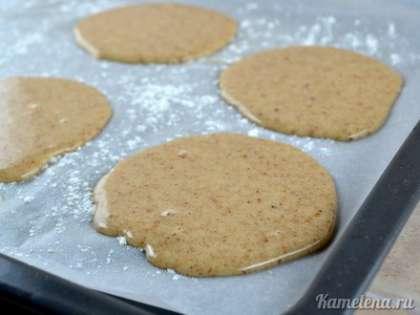 На противень постелить пекарскую бумагу, хорошо смазать ее маслом, и слегка присыпать мукой (обычно бумагу смазывать не надо, но так как в тесте нет масла, то большая вероятность, что печенье может прилипнуть). Выложить тесто ложкой в 6 горок по всему противню (тесто растечется в довольно широкие круги).  Поставить в разогретую до 180 градусов духовку. Выпекать 15-17 минут.