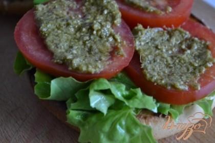 Уложить салатные листья, кружочки томатов и песто.