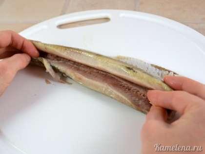 Далее селедку надрезать вдоль спинки, и разделить на две половинки. Вынуть хребет, с реберными костями.