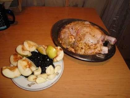 Курицу смазать солью и перцем. Яблоки почистить и порезать дольками, чеснок почистить, чернослив вымыть