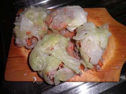 На середину каждого подготовленного капустного листа положить 1 столовую ложку фарша (мяса с рисом) и свернуть конвертиком или трубочкой.