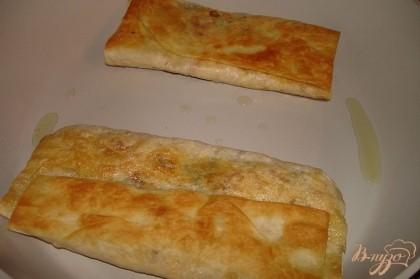 На полоску лаваша выложить сыр, зелень и колбасу. На фото начинка вся лежит по центру. Это не так. Начинку следует распределить по всей поверхности лаваша. Фото, на котором это было показано - не получилось. Увы. Итак, тонким слоем распределите начинку по всей внешней поверхности лаваша. Добавьте специй по вкусу. Учтите, что и в сыре и в колбасе соли достатночо. Выбирайте специи без соли. На сковороде с антипригарным покрытием обжариваем лаваш. В сковороду предварительно добавить немного растительного масла. Напомню, что мы не готовим пирожки во фритюре. Это всего лишь легкая обжарка, целью которой является слегка подрумянить и подсушить лаваш, при этом сыр внутри лаваша должен успеть расплавится. Итак, постоянно под крышкой в сковороде обжариваем лаваш с двух сторон. Огонь небольшой.