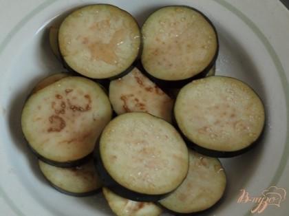 Нарезать баклажаны  кружочками толщиной около 0.7 см и выложить их  на пекарскую бумагу.Сбрызнуть оливковым маслом и запечь в духовке около 20 минут при 180 гр.
