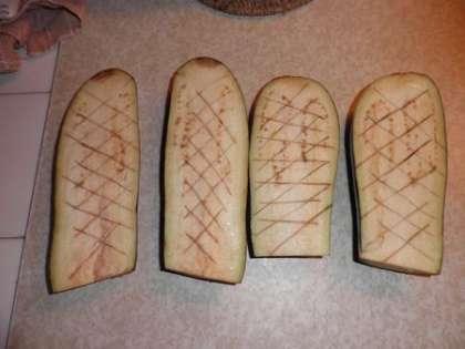 Баклажаны разрезать вдоль, сделать ножом «сетку», посолить и оставить на 20 минут