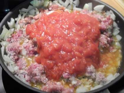 Обжарить лук с фаршем, томатами и специями