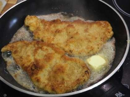 Когда шницели будут почти готовы, добавить на сковороду сливочное масло и обжарить с каждой стороны еще по минуте