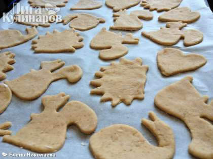 Вырезаем печенье любыми формочками, можно обычными кружочками. И выкладываем на противень, застеленный пергаментом для выпечки