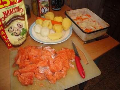 На картофель выложить слой моркови, а сверху слой лука. Рыбу порезать среднего размера квадратиками