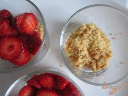 На дно каждой порции покрошить печенье и выложить ягоды клубники.