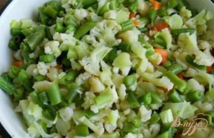 Бланшированные овощи откинуть на дуршлаг, затем мелко нарезать вместе с фасолью (или добавить горошек).