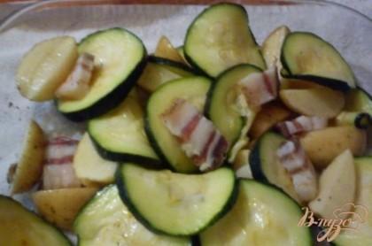 Картофель порезать на половинки,натереть солью и перцем и смазать ароматным маслом, выложить в форму, между дольками картошки разложить цукини и кусочки сала, поставить в духовку при температуре 230 на 45 минут до готовности.