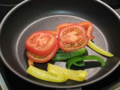 Положить на сковородку помидоры и перцы, обжарить на маленьком огне перемешивая примерно 1,5 минуты